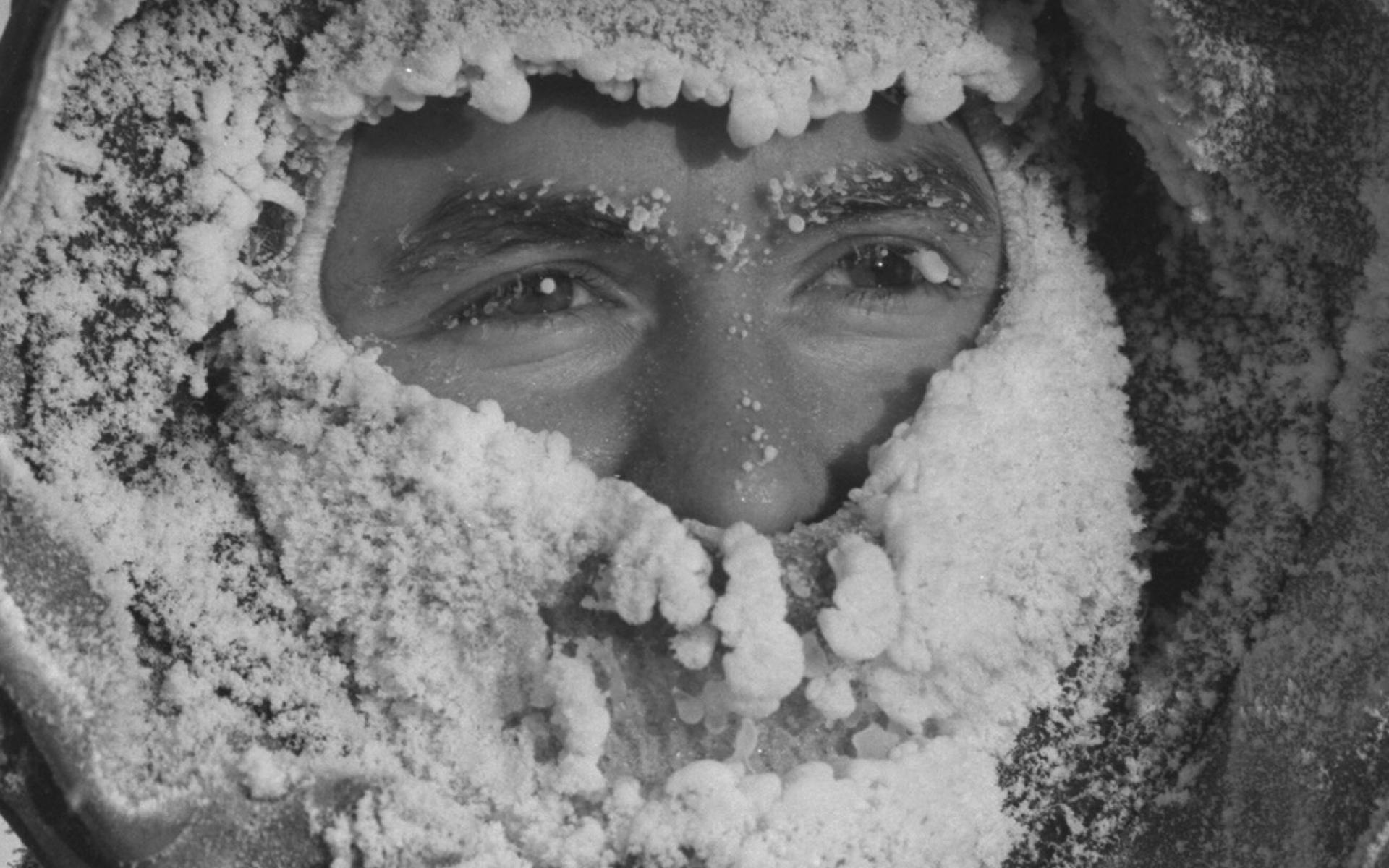 L'hydrographe Ralph Courtnage, capuchon de parka et cagoule gelés par la respiration, travaille sur la glace de mer.