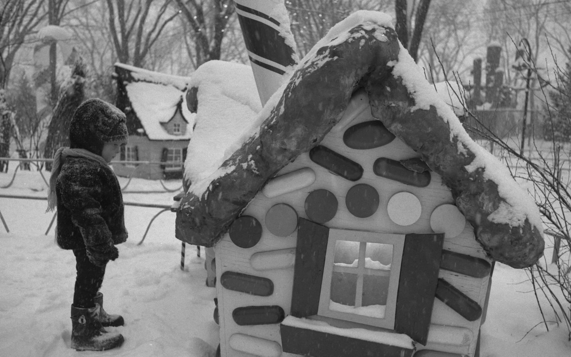 Un jeune enfant en vêtements d'hiver regarde une maisonnette en bonbons.