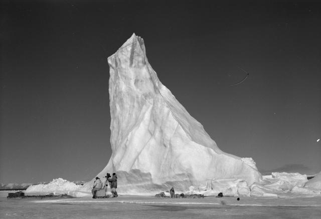 Une équipe de l'Office national du film installe sa caméra près d'un haut iceberg arctique.