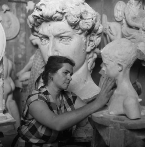 "Artist Sylvia Lefkovitz examining original clay head of the bronze, ""David"""